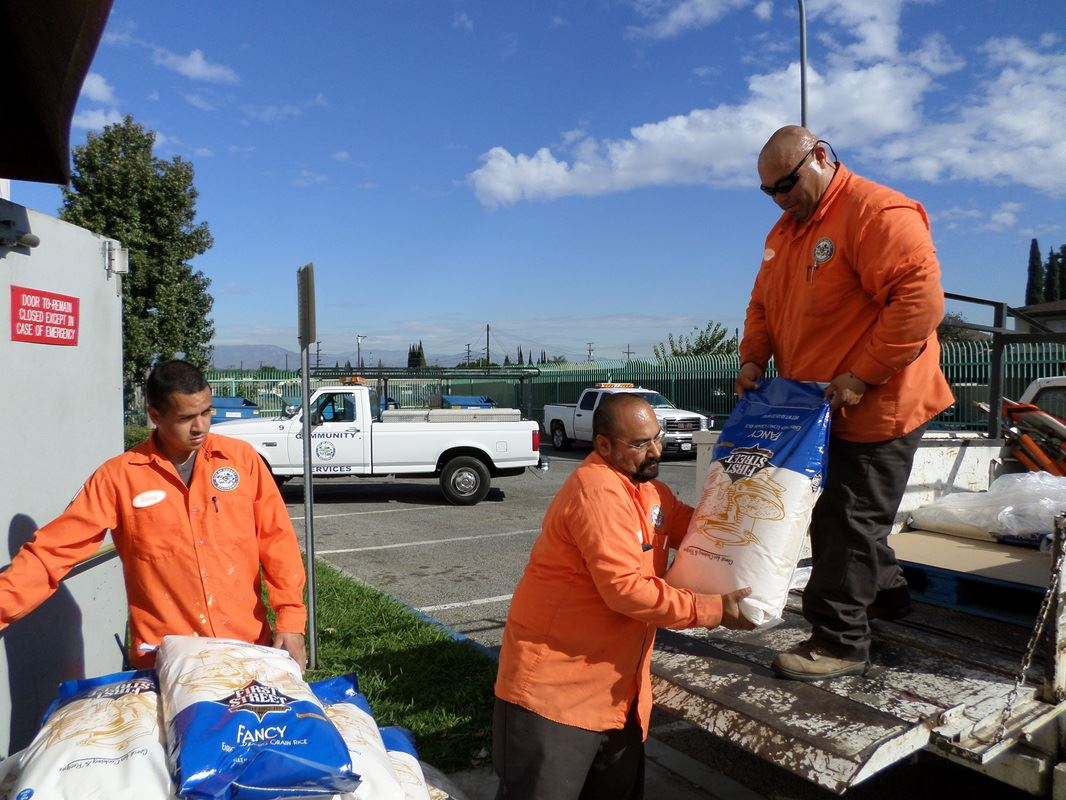 Public safety workers moving large bags from a pickup to a pile.